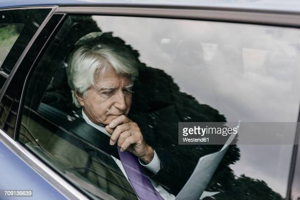 Senior businessman reading documents in a car