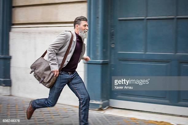 Senior businessman running on city street