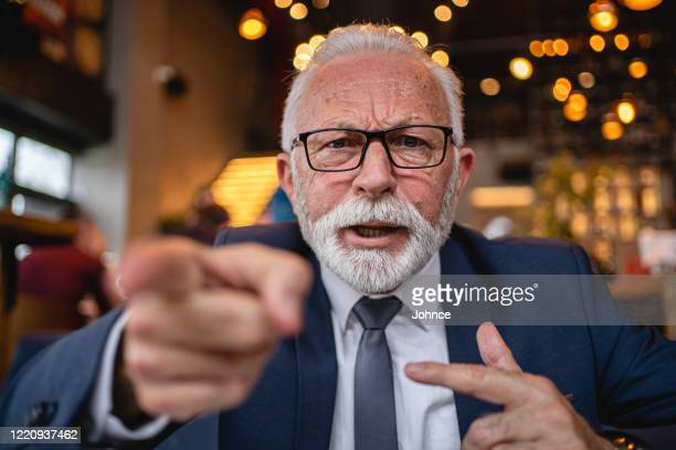 senior businessman shouting into the camera - shouting stock pictures, royalty-free photos & images