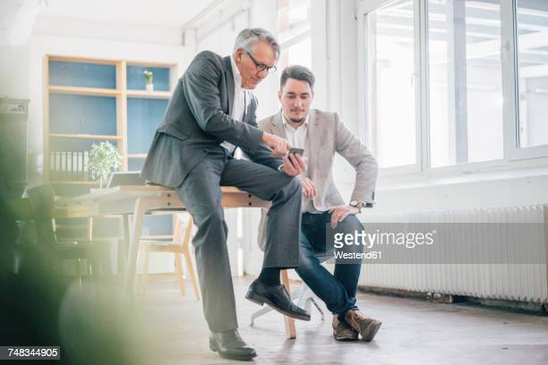 senior businessman showing cell phone to young businessman - two generation family stock pictures, royalty-free photos & images