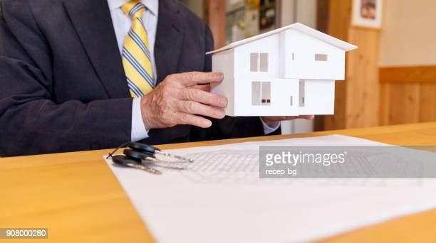senior businessman showing small model house - real estate office stock photos and pictures