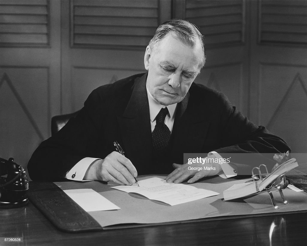 Senior businessman signing papers at desk, (B&W), close-up : Stock Photo