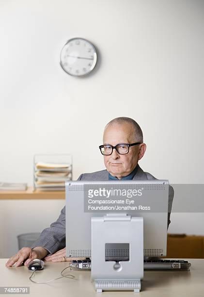 Senior businessman sitting at desk in office, using computer, portrait