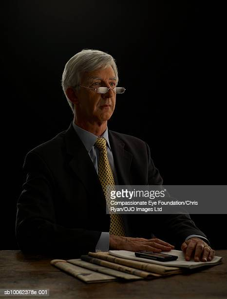 """senior businessman sitting at desk with newspaper, looking away - """"compassionate eye"""" stock pictures, royalty-free photos & images"""