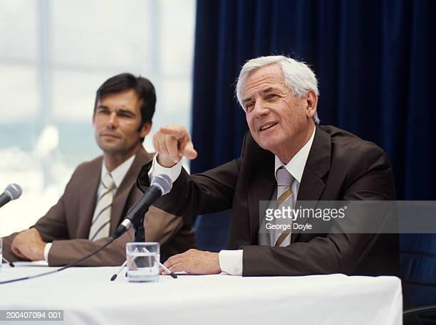 senior businessman sitting by mic, pointing - 背広 ストックフォトと画像