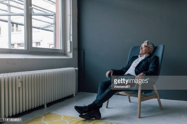 senior businessman sitting in armchair looking out of the window - armchair stock pictures, royalty-free photos & images