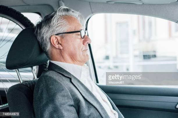 Senior businessman sitting in car with closed eyes