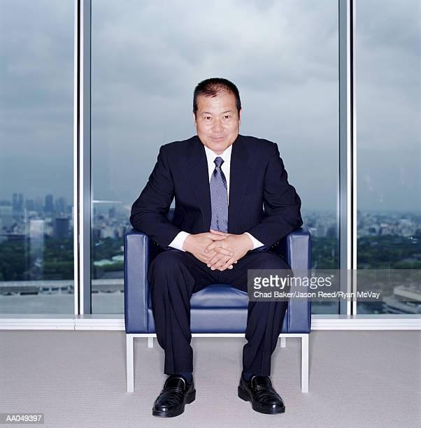 Senior businessman sitting in chair, hands clasped, portrait