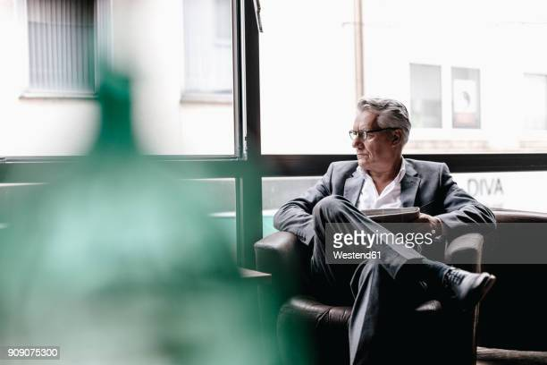senior businessman sitting in chair, reading newspaper - respekt stock-fotos und bilder