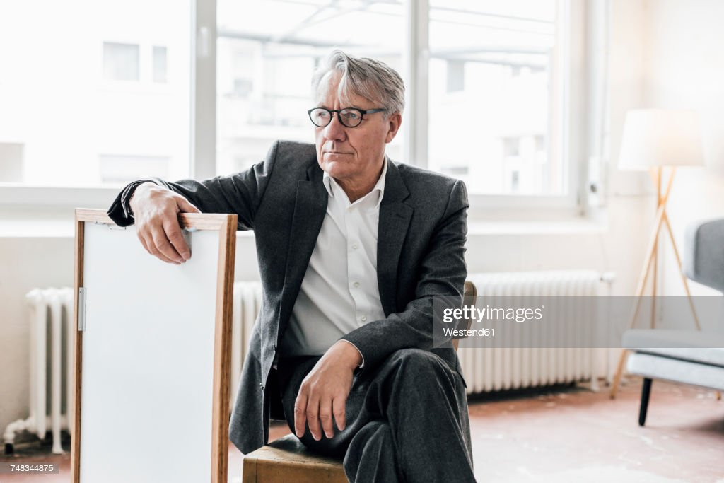 Senior businessman sitting on chair with picture frame : ストックフォト