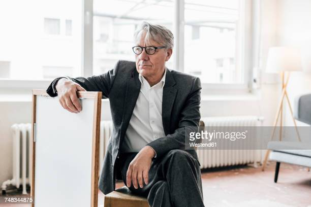 senior businessman sitting on chair with picture frame - art dealer stock pictures, royalty-free photos & images