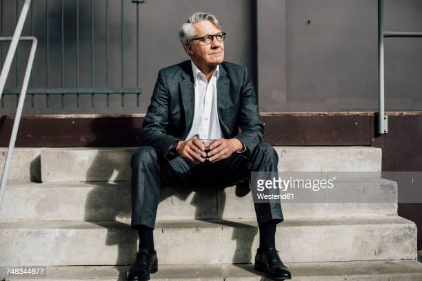 senior businessman sitting on concrete stairs - geschäftskleidung stock-fotos und bilder