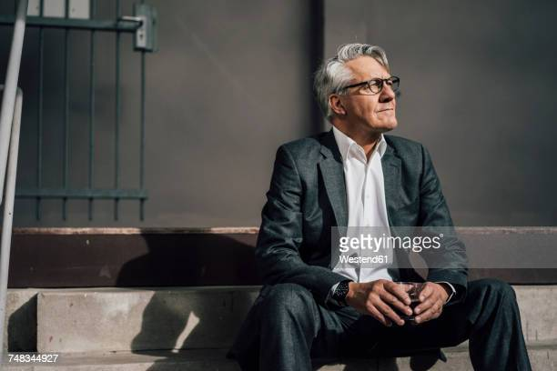 senior businessman sitting on concrete stairs - three quarter length stock pictures, royalty-free photos & images