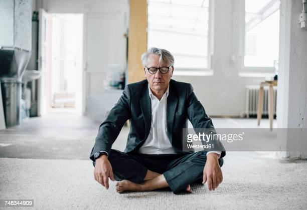 senior businessman sitting on floor meditating - meditieren stock-fotos und bilder