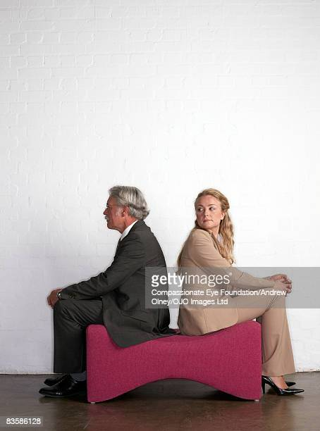 Senior businessman sitting with businesswoman