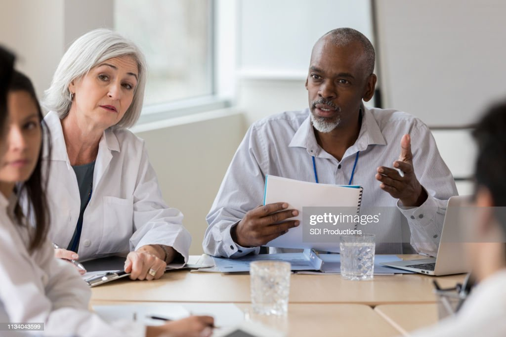 Senior businessman speaks seriously with medical staff : Stock Photo