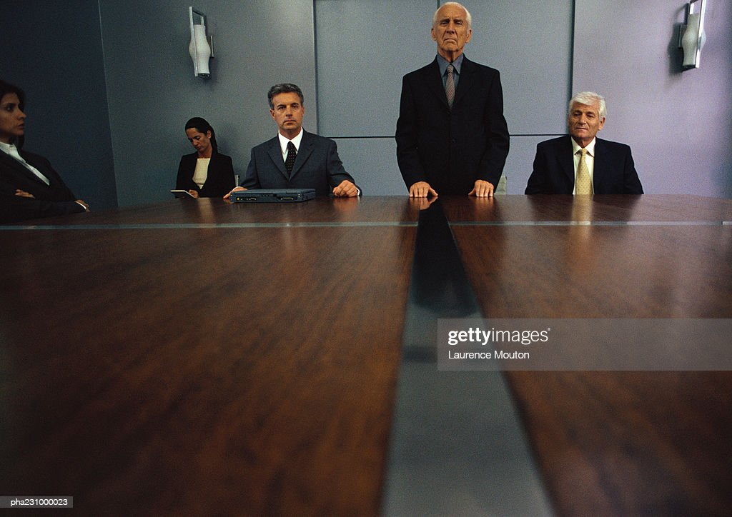 Senior businessman standing at conference table while others are seated, long shot : Stockfoto