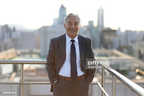 senior businessman standing on rooftop - businesswear stock-fotos und bilder