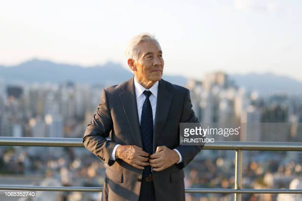 Senior businessman standing on rooftop