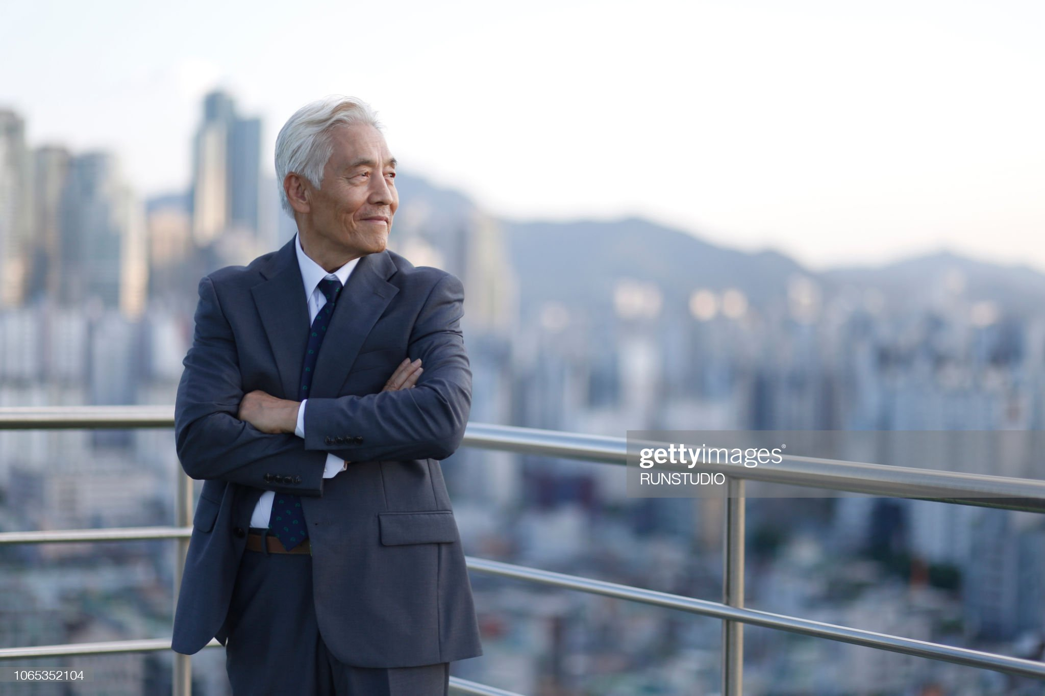 Senior businessman standing with arms crossed on rooftop : ストックフォト