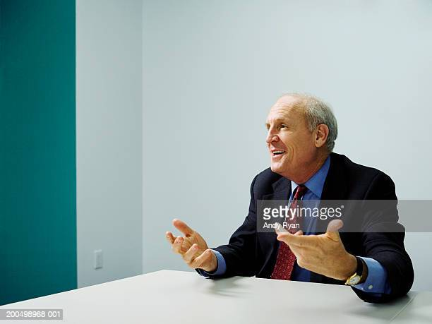 senior businessman talking in meeting, making hand gestures, smiling - gesturing stock pictures, royalty-free photos & images