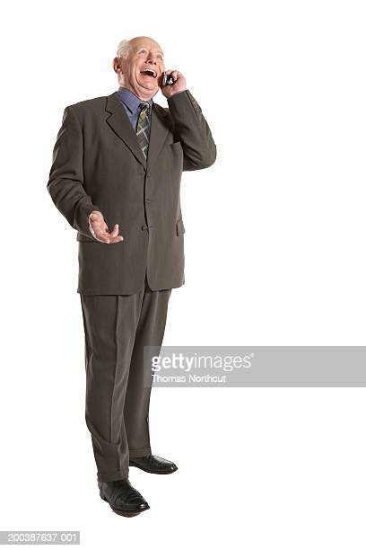 Senior businessman talking on cell phone, looking up, laughing