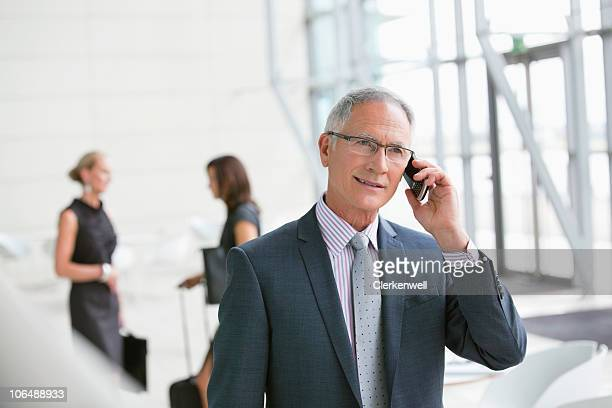 Senior businessman talking on mobile phone with colleagues in background