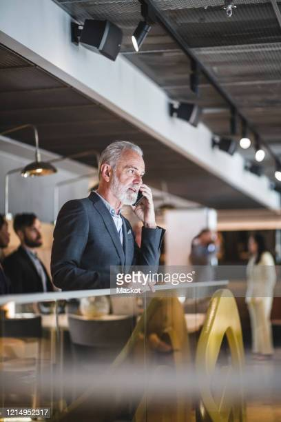 senior businessman talking on smart phone while standing by railing in office - incidental people stock pictures, royalty-free photos & images