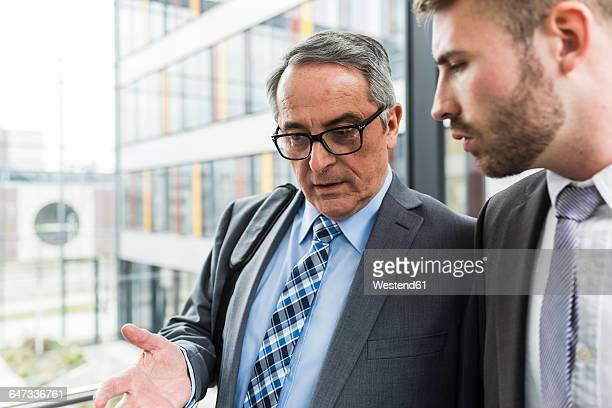 Senior businessman talking to young businessman