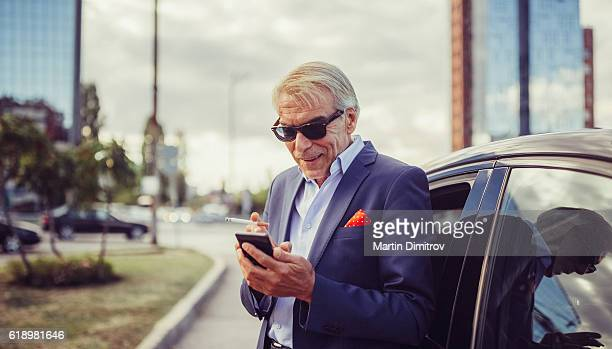 Senior businessman texting in the city