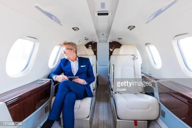 企業ジェット機で旅行するシニアビジネスマン - 自家用飛行機 ストックフォトと画像