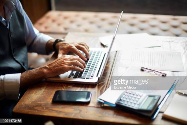 senior businessman typing on a laptop in a coworking space - financial advisor stock pictures, royalty-free photos & images
