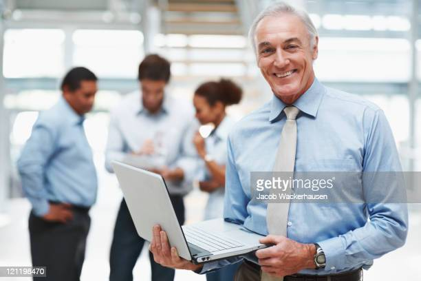 senior businessman using a laptop with colleagues at the back - banker stock photos and pictures