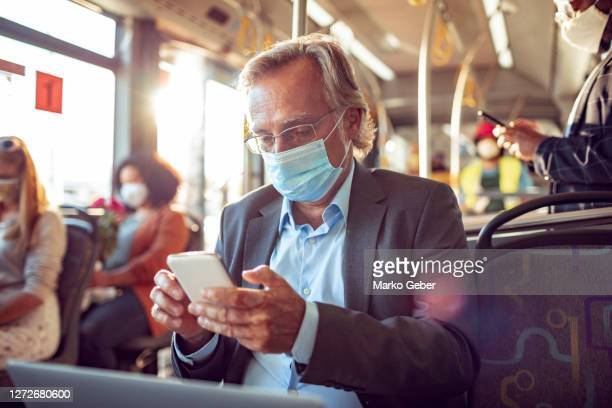 senior businessman using a phone while commuting on a bus - travel stock pictures, royalty-free photos & images