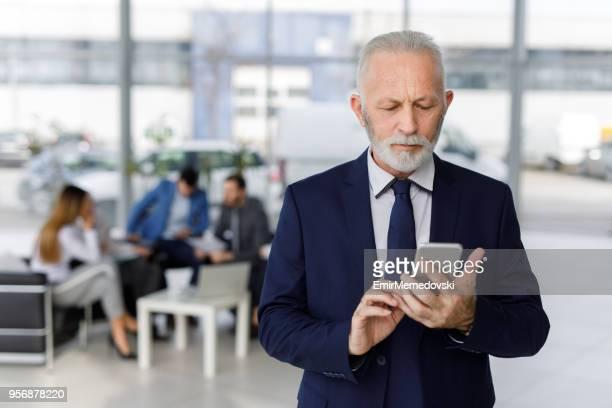 Leitender Geschäftsmann mit Handy