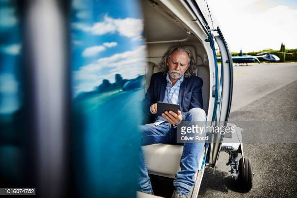 senior businessman using digital tablet in helicopter on airfield - premium access stock pictures, royalty-free photos & images