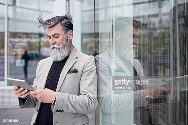 Senior Geschäftsmann mit Digitaltablett in Bürogebäude
