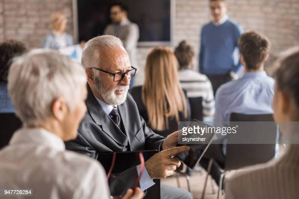 senior businessman using digital tablet with his colleagues during seminar in board room. - business conference stock pictures, royalty-free photos & images