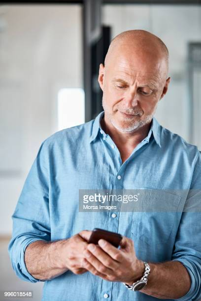Senior businessman using mobile phone at office