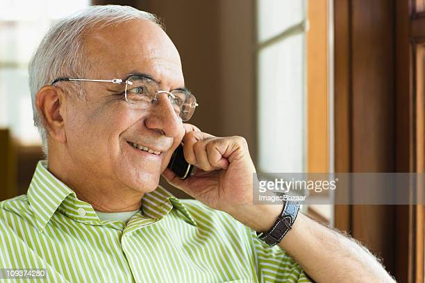 Senior businessman using mobile phone, smiling