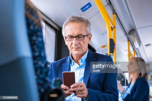 senior businessman using phone in bus - izusek stock pictures, royalty-free photos & images