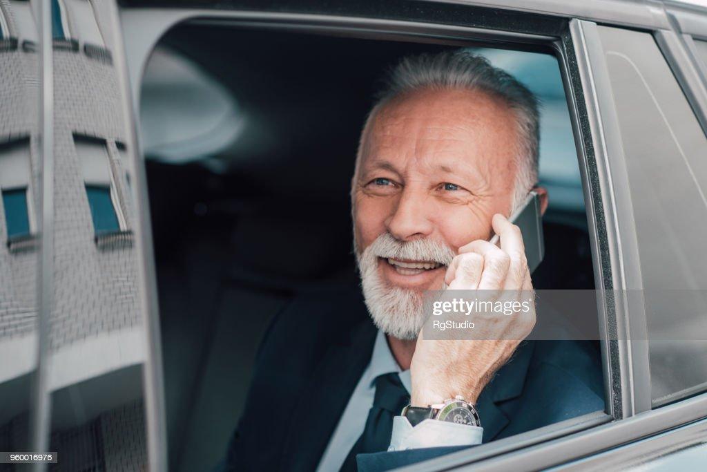 Leitenden Geschäftsmann mit Telefon in Business-Fahrzeug : Stock-Foto