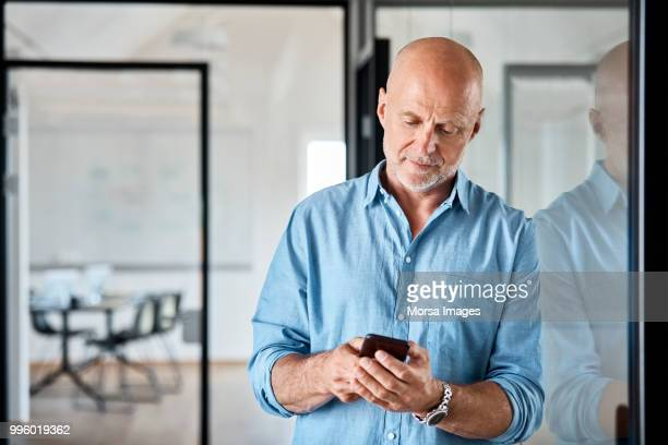 Senior businessman using smart phone at office