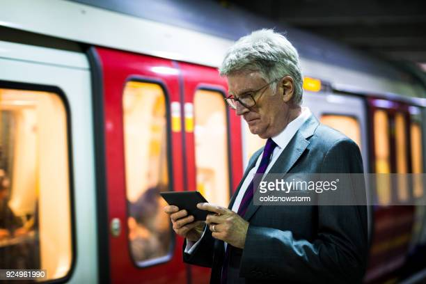 Senior businessman waiting for a train and looking at his digital tablet