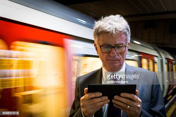 Senior businessman waiting for an underground train and looking at his digital tablet, London, UK