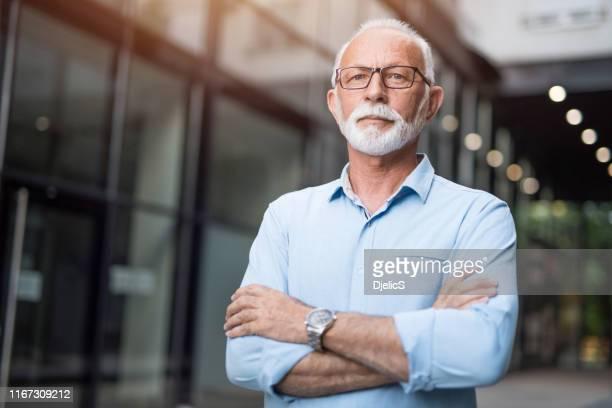 un hombre de negocios de alto rango con los brazos cruzados mirando la cámara. - 60 64 años fotografías e imágenes de stock