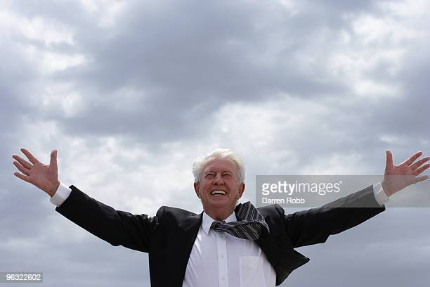 Senior businessman with arms outstretched, smiling