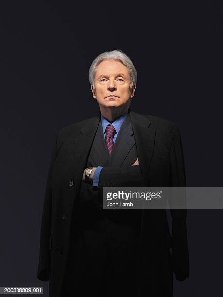 senior businessman with coat around shoulders, arms folded, portrait - mafia stock pictures, royalty-free photos & images