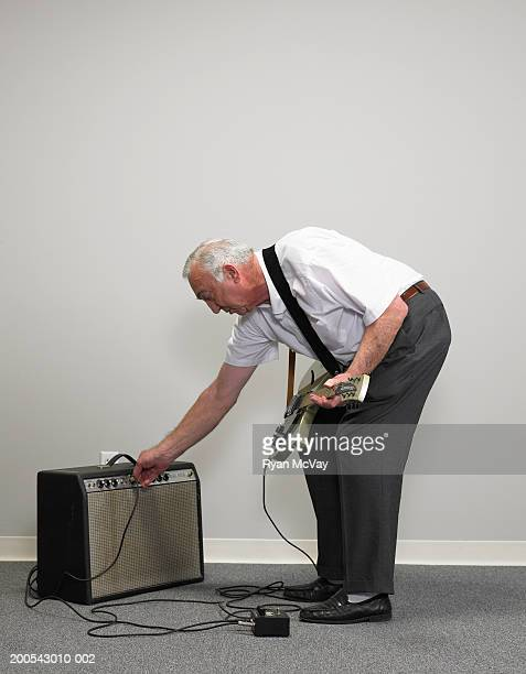 Senior businessman with electric guitar adjusting amplifier