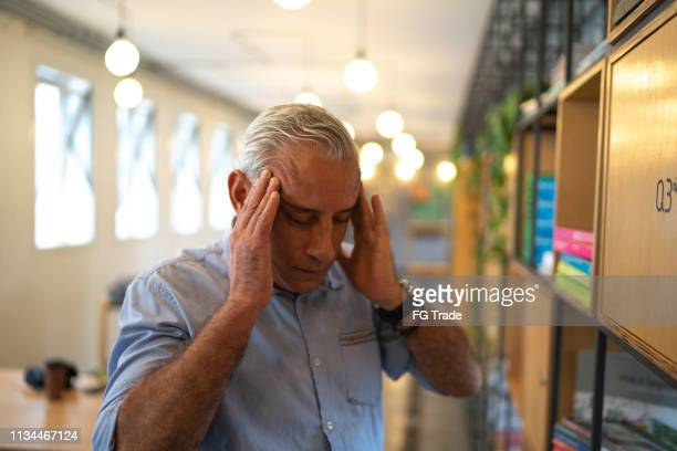 homem de negócios sênior com dor de cabeça no trabalho - carregando - fotografias e filmes do acervo